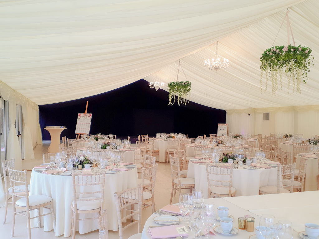 Interior of a wedding marquee with staged tables, cream linings, chandeliers and a feature starlight lining in the background